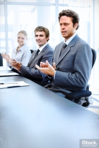 Successful applauding executives sitting at the table